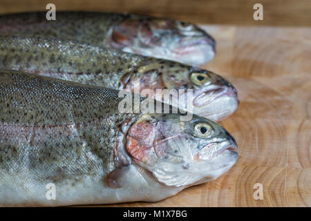 Three fresh, dead, uncooked, raw rainbow trout on wooden chopping board in kitchen - Stock Photo