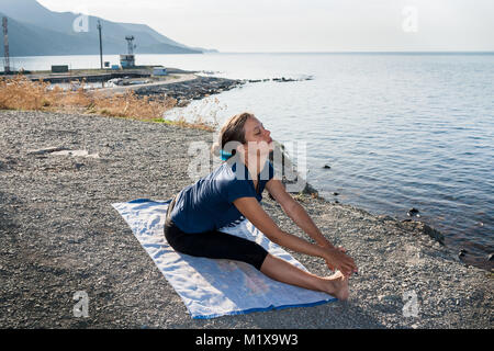 Young girl is doing yoga sitting on a stony sea coast in summer morning. - Stock Photo