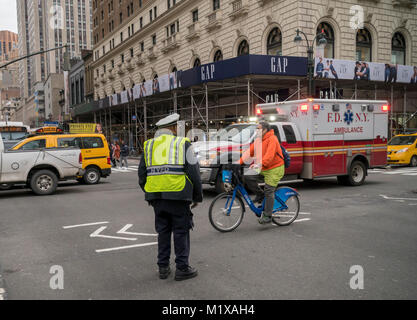 An NYPD traffic enforcement agent allows an ambulance to pass through in Herald Square in New York on Saturday, - Stock Photo