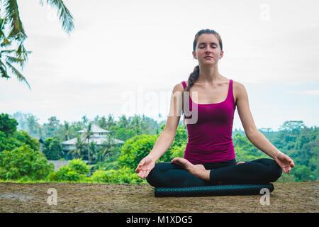 Woman meditates in yoga asana Padmasana - Stock Photo