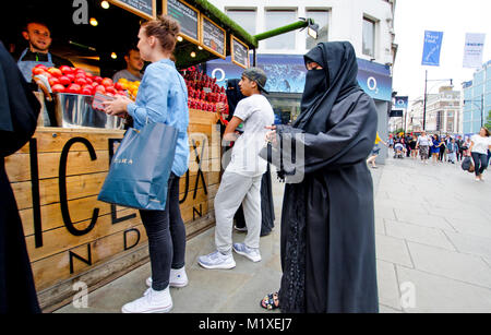 London, England, UK. Muslim woman in full-length Islamic dress at a stall selling fruit - Stock Photo
