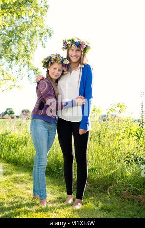 Sisters wearing midsummer crowns in Kollandso, Sweden - Stock Photo