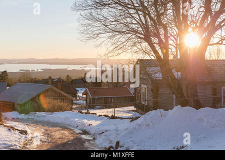 Sunrise over houses in Dalarna, Sweden during winter - Stock Photo