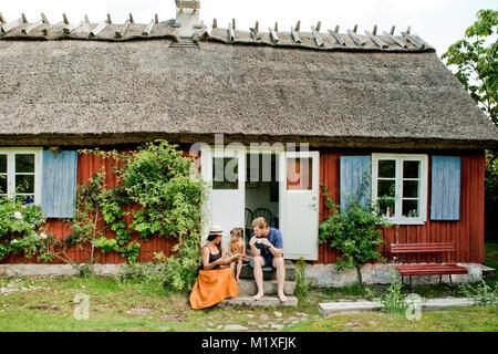 Family sitting on steps in Friseboda, Sweden - Stock Photo