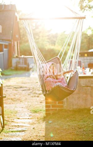 Girl in hammock at sunset in Friseboda, Sweden - Stock Photo
