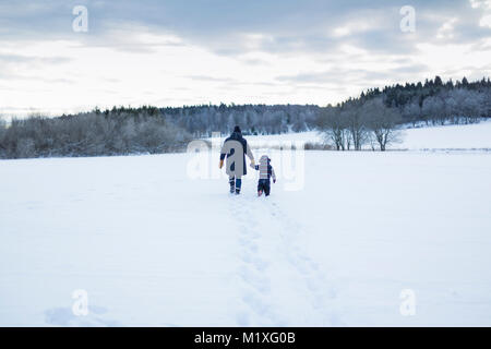 Rear view of mother and child walking in snow - Stock Photo