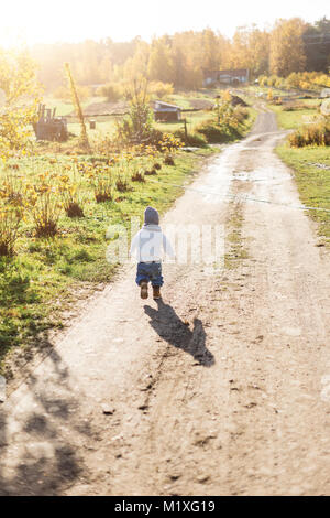 Rear view of little boy playing on a rural road in Sweden - Stock Photo