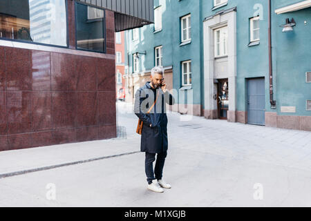 Man on smart phone on street in Stockholm, Sweden - Stock Photo