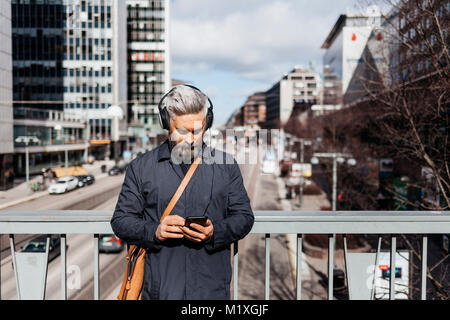 Man with smart phone on street in Stockholm, Sweden - Stock Photo
