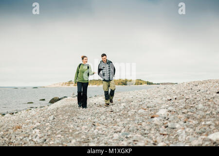 Couple walking along rocky coastline in Stockholm, Sweden - Stock Photo