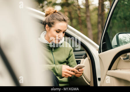 Young woman sitting in car on smart phone in Sweden - Stock Photo