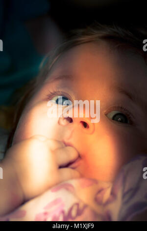 Curious look of a cute baby. Cute looking child. A sunlight on the child's face. Newborn. A curious look of a little - Stock Photo