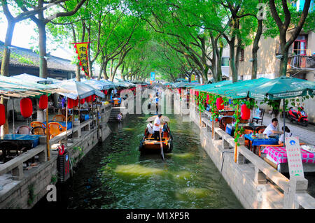 July 25, 2015. Tongli Town, China.  A tourist boat moving by a coffee house on the water canals within Tongli Town - Stock Photo