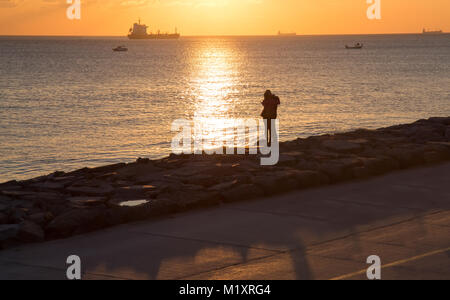 Young couple silhoutte during the sunset near the sea on the rocks reverse light image - Stock Photo