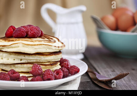 Delicious homemade golden pancakes with fresh raspberries. Extreme shallow depth of field. - Stock Photo
