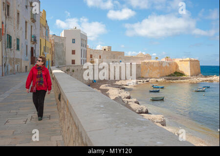 Woman solo tourist, a mature woman traveler walks along the sea wall on the north shore of Trapani, Sicily. [MODEL - Stock Photo