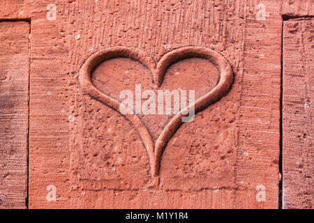 Love sign. Heart shaped in relief on a old brick wall in France - Stock Photo