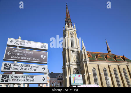 NOVI SAD, SERBIA - APRIL 03: Catholic Cathedral and Tourist signpost street indicating, which in this city keeps - Stock Photo