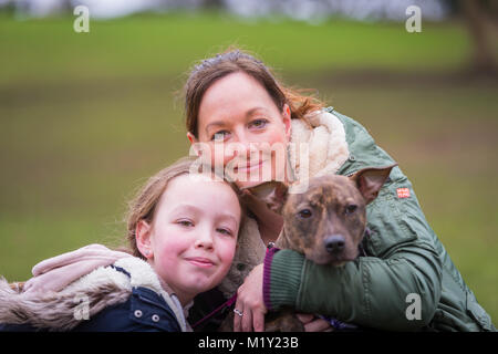 Woman with her daughter and their pet staffordshire bull terrier dog in the park smiling - Stock Photo