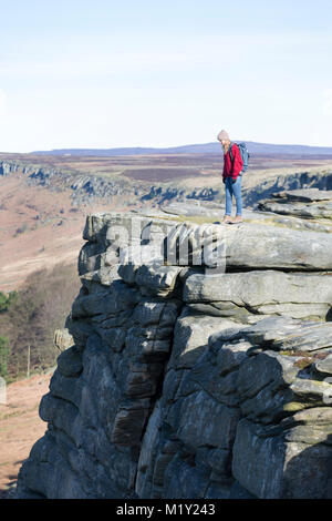 UK, Derbyshire, Peak District Nationa Park, a walker on the cliff edge of Stanage Edge. - Stock Photo
