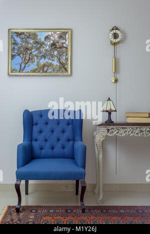 Vintage Furniture - Interior composition of retro blue armchair, vintage wooden beige table, table lamp, books, - Stock Photo