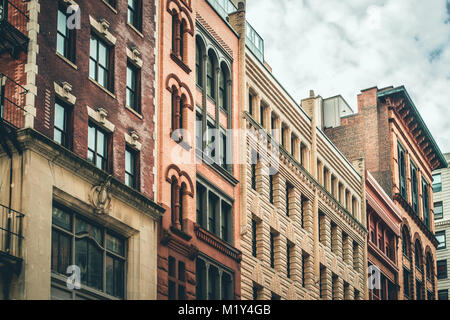 Row of vintage New York City apartment buildings in a variety of brick and brownstone facades - Stock Photo