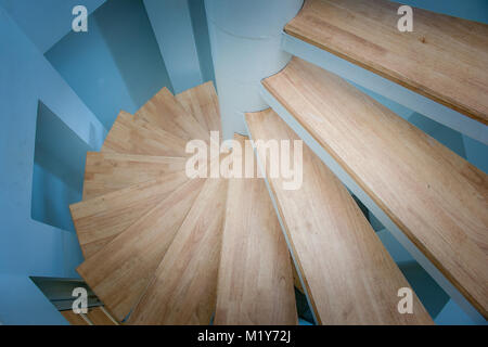 Top view of spiral wooden staircase surrounded with blue wall in lighthouse. - Stock Photo