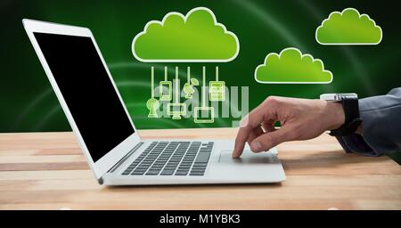 Hand using laptop with clouds icon and hanging connection devices and green background - Stock Photo