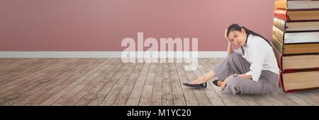 Business woman sitting on the floor next to a pile of books - Stock Photo