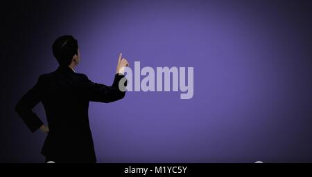 Businessman pointing on purple - Stock Photo