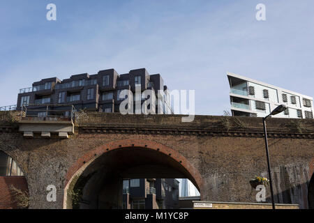 Old Victorian railway bridge and new housing in the borough of Southwark, on 30th January 2018, in London, England. - Stock Photo