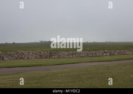 View across a dry stone wall to misty green field with a white house on the horizon - Stock Photo