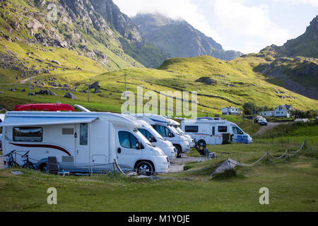 A number of RV:s or motorhomes are parking overnight at the parking lot at Haukland Beach, Lofoten, Norway. - Stock Photo