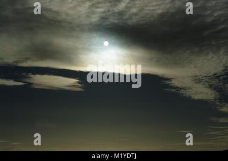 Weak Sun Shines through Maceral Altocumulus Clouds in a Spooky Abstract, Dark yet Glowing Effect. British Weather, - Stock Photo