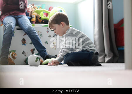Young boy counting money from piggy bank on bedroom floor - Stock Photo