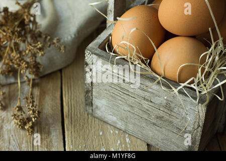 Brown Organic Eggs on Straw in Vintage Wooden Box on Plank Kitchen Table Linen Napkin Dry Flowers. Easter Composition - Stock Photo