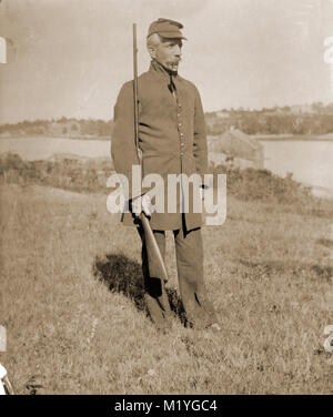 Antique circa 1905 photograph, elderly gentleman with rifle in military uniform. Location is in or near Riggsville - Stock Photo