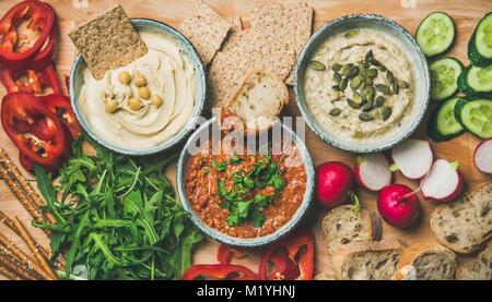Vegan snack board. Flat-lay of various Vegetarian dips hummus, babaganush and muhammara with crackers, bread and - Stock Photo