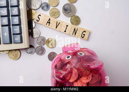 SAVING CONCEPT. Red piggy bank and coins with word SAVING on wooden plates. - Stock Photo