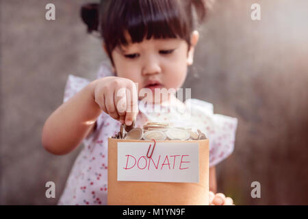 Child with Donation Concept. 2 Years Old Child putting Money Coin into a Donate Box - Stock Photo