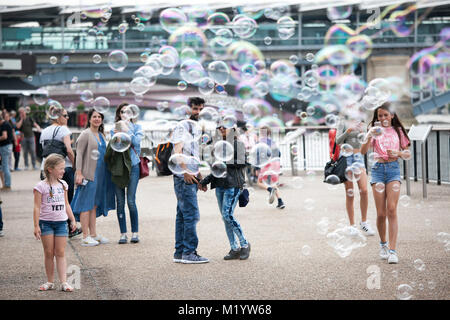 LONDON, ENGLAND - AUGUST 22, 2017 People run through soap bubbles - Stock Photo