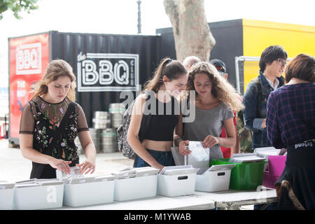 LONDON, ENGLAND - AUGUST 22, 2017 Young girls at second hand book stall - Stock Photo