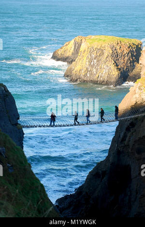 Friends crossing the rope bridge in carrick-a-rede, County Antrim, Northern Ireland, UK - Stock Photo
