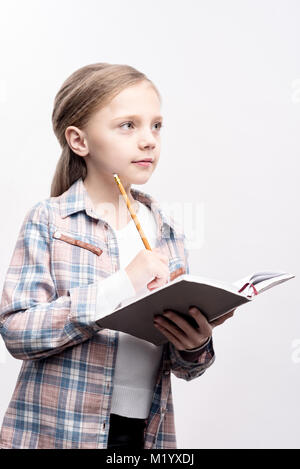 Cute little girl posing with notebook and pencil - Stock Photo