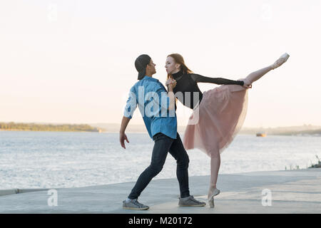 A young couple in love passionately dances on the embankment of the city. Dancer and sportsman Parkour. Date of - Stock Photo