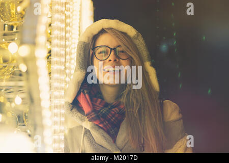 A young attractive hipster girl in glasses and a warm scarf walks by the mall on a holiday. She smiles and laughs. - Stock Photo