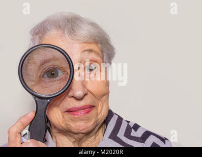 portrait of senior woman looking through a magnifying glass over white background - Stock Photo