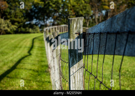 Aged farm fence in a grass field - Stock Photo