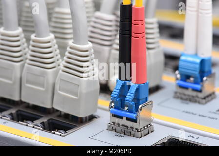 Optic fiber and network cables connected to switch in data center, internet network technology - Stock Photo
