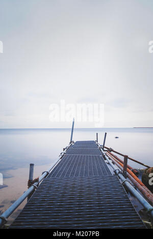 Silky sea view from metal pier, long exposed image - Stock Photo